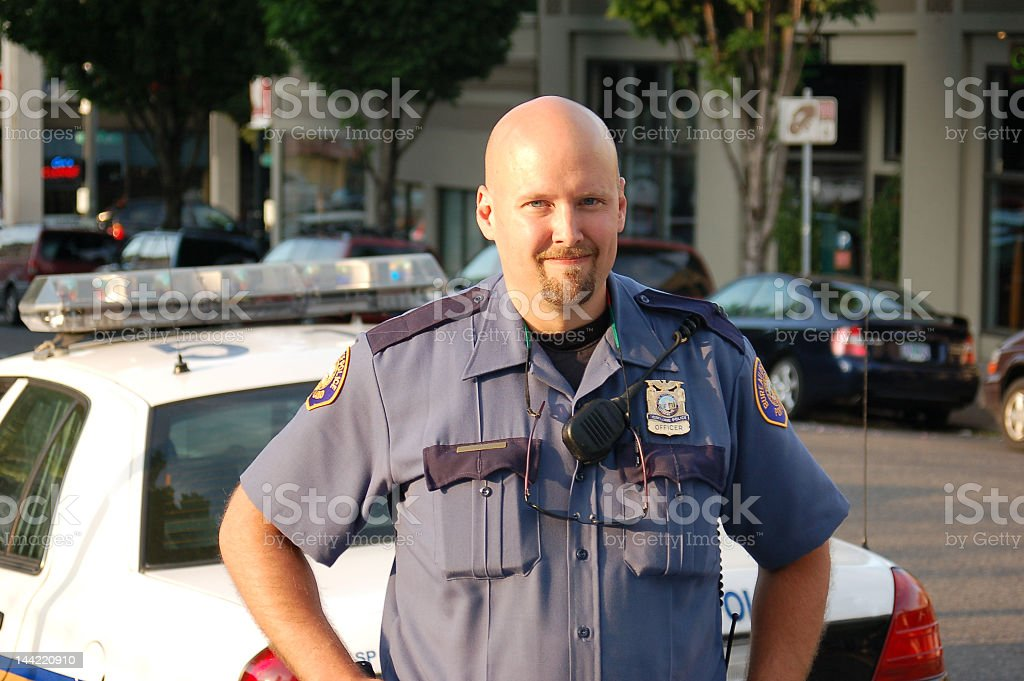 A smiling police officer in front of his squad car  royalty-free stock photo