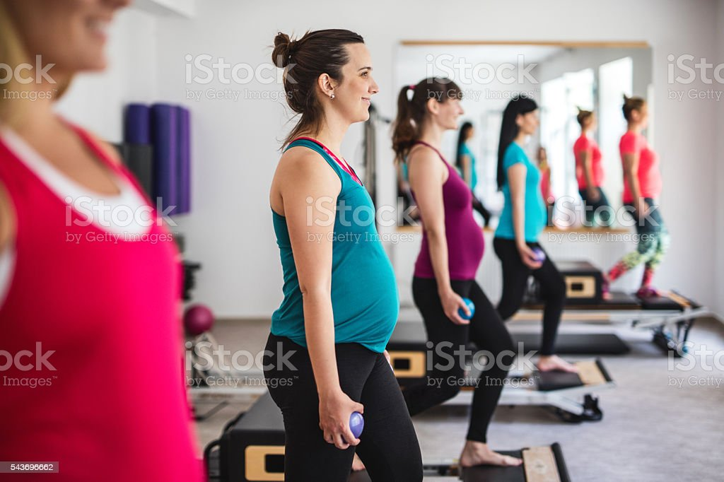 Group of pregnant women exercising with balls in health club. Focus...