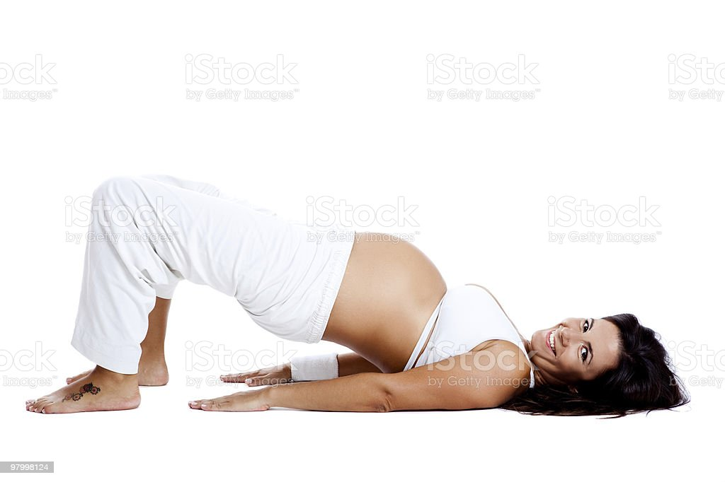 Smiling pregnant woman laying on the ground doing exercises royalty-free stock photo