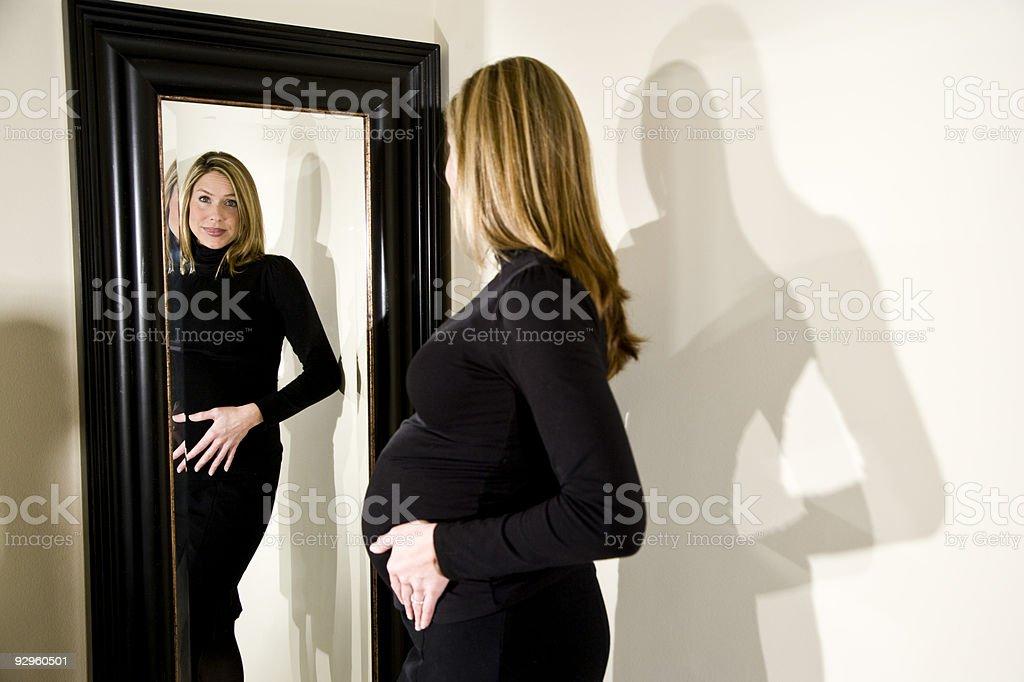 Sonriente mujer embarazada mirando a sí misma en el espejo foto de stock libre de derechos