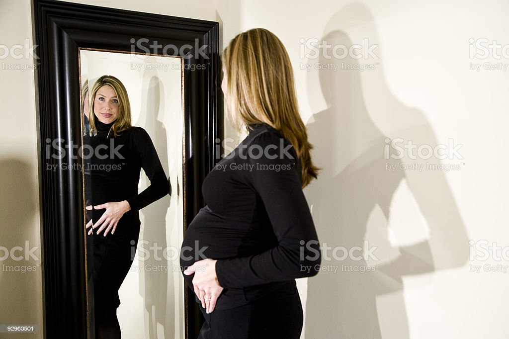 Smiling pregnant woman looking at herself in mirror stock photo