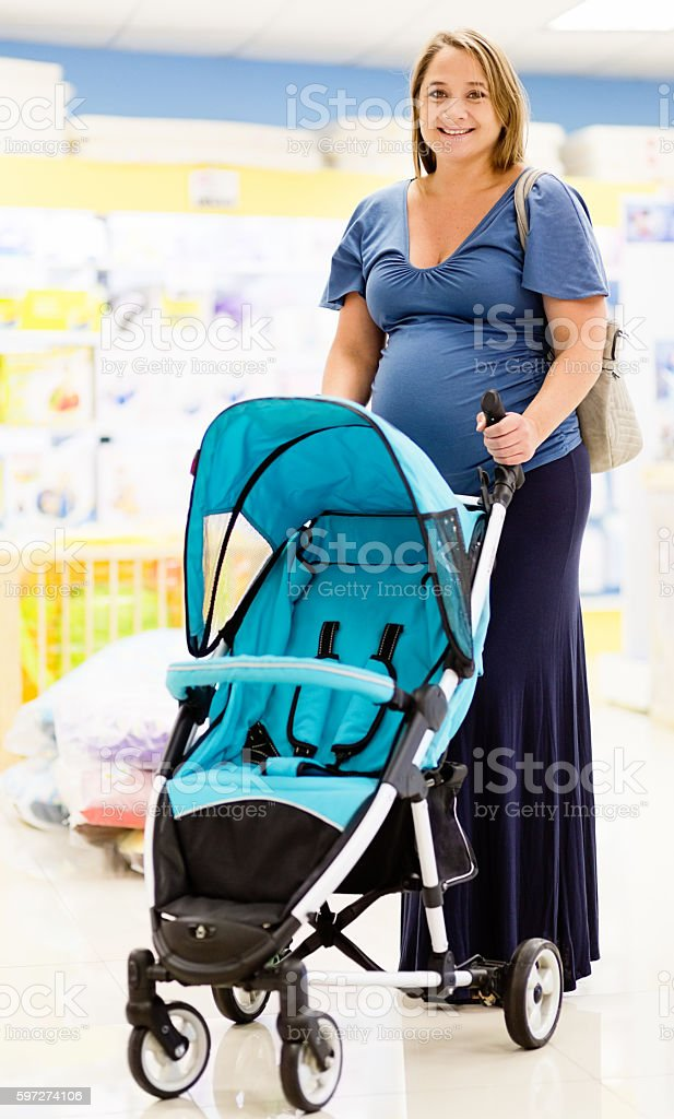 Smiling pregnant woman selecting stroller in baby store stock photo