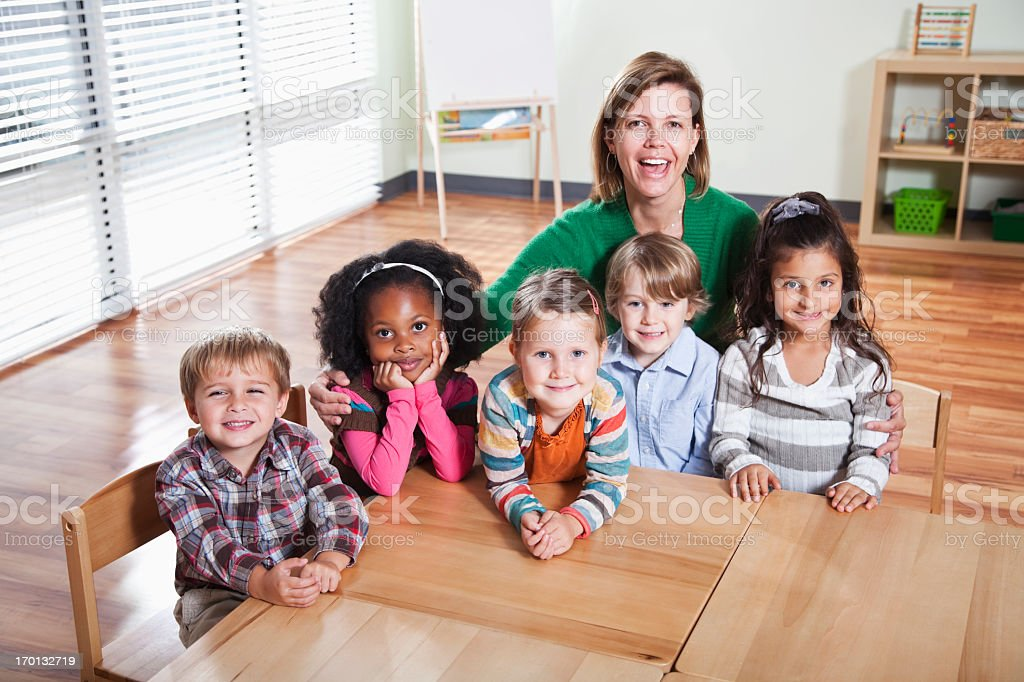Smiling preschoolers and teacher sitting at table stock photo