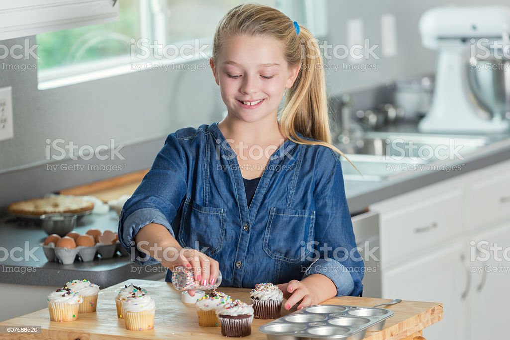 Smiling preteen girl using sprinkles to decorate cupcakes stock photo
