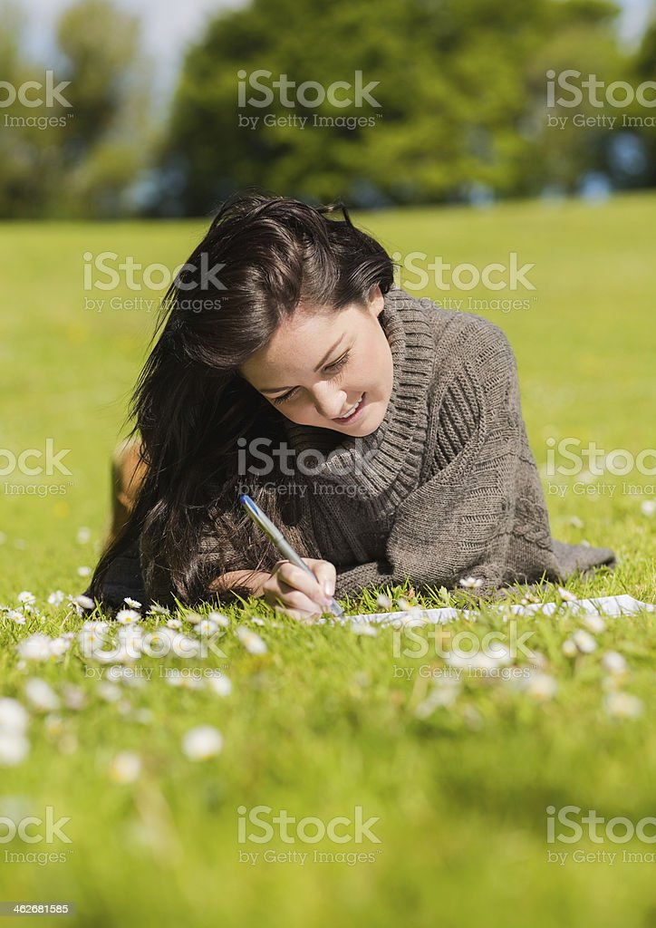 Smiling pretty brunette writing while lying on the grass royalty-free stock photo