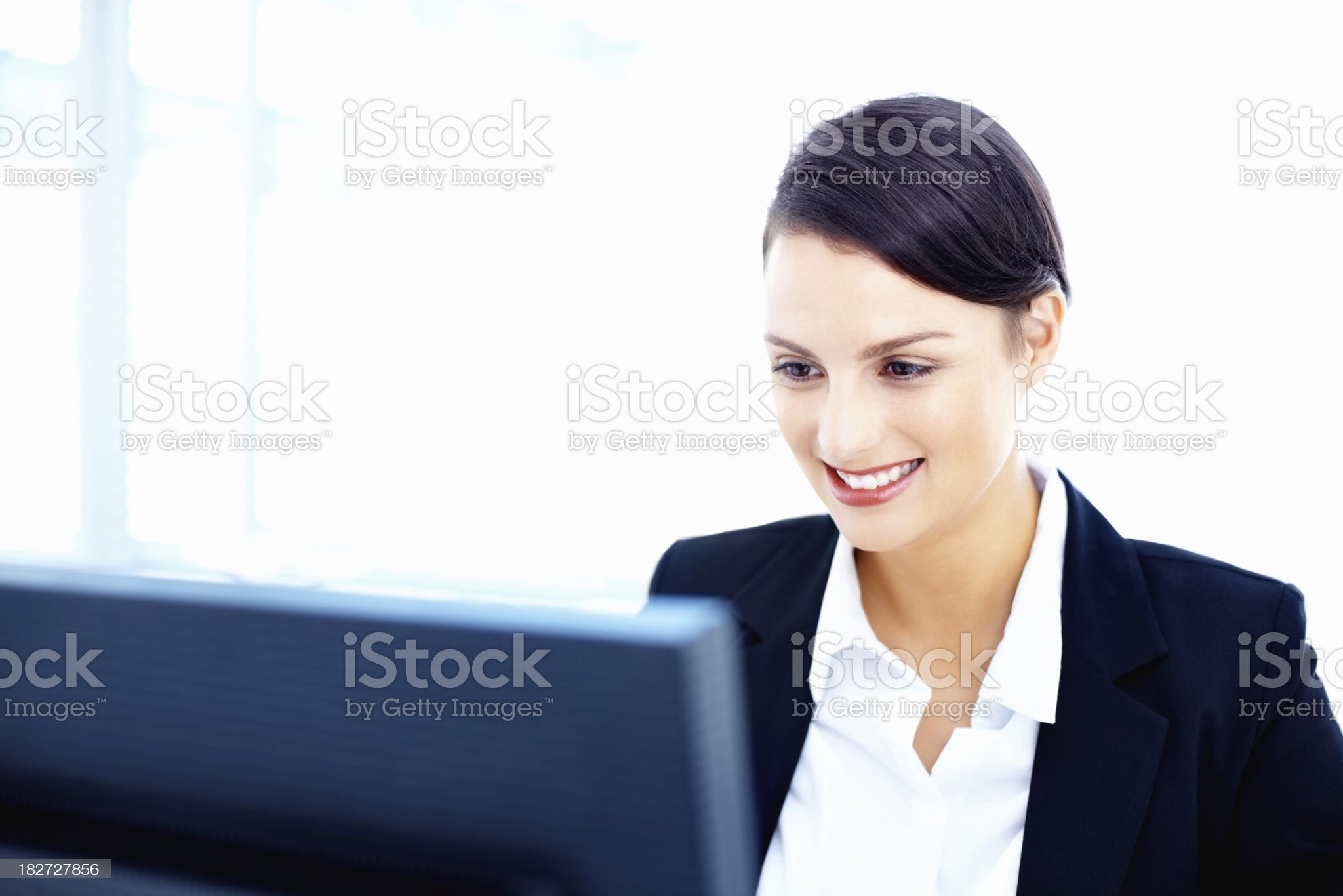 Smiling pretty business woman using a computer against white royalty-free stock photo