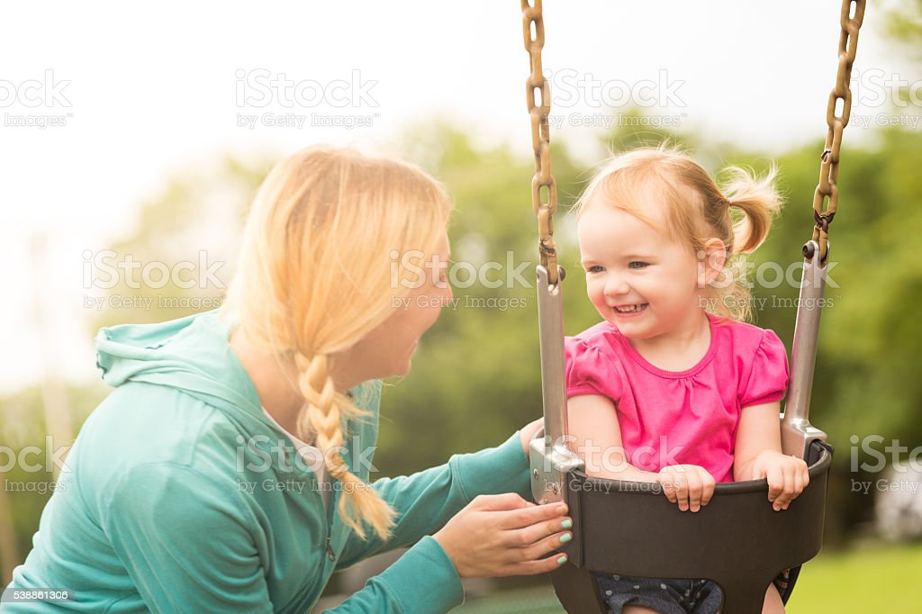 Smiling pretty toddler girl on swing stock photo