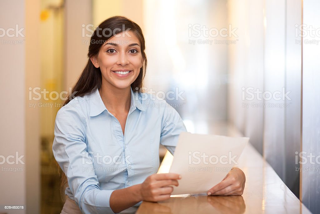 Smiling Pretty Woman Holding Document in Cafe stock photo