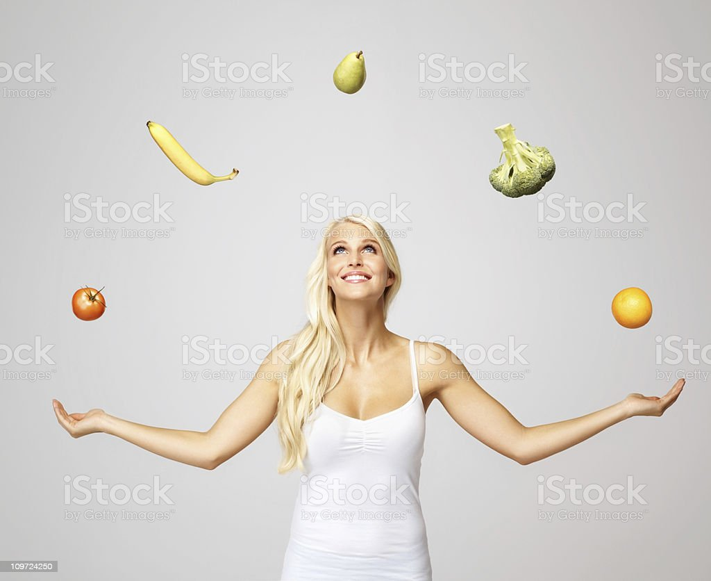 Smiling pretty woman juggling fruits and vegetables stock photo