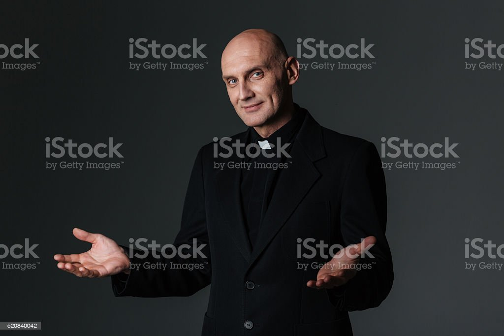 Smiling priest standing and inviting you stock photo