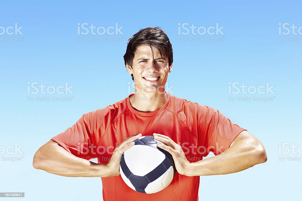 Smiling pro footballer holding a football royalty-free stock photo