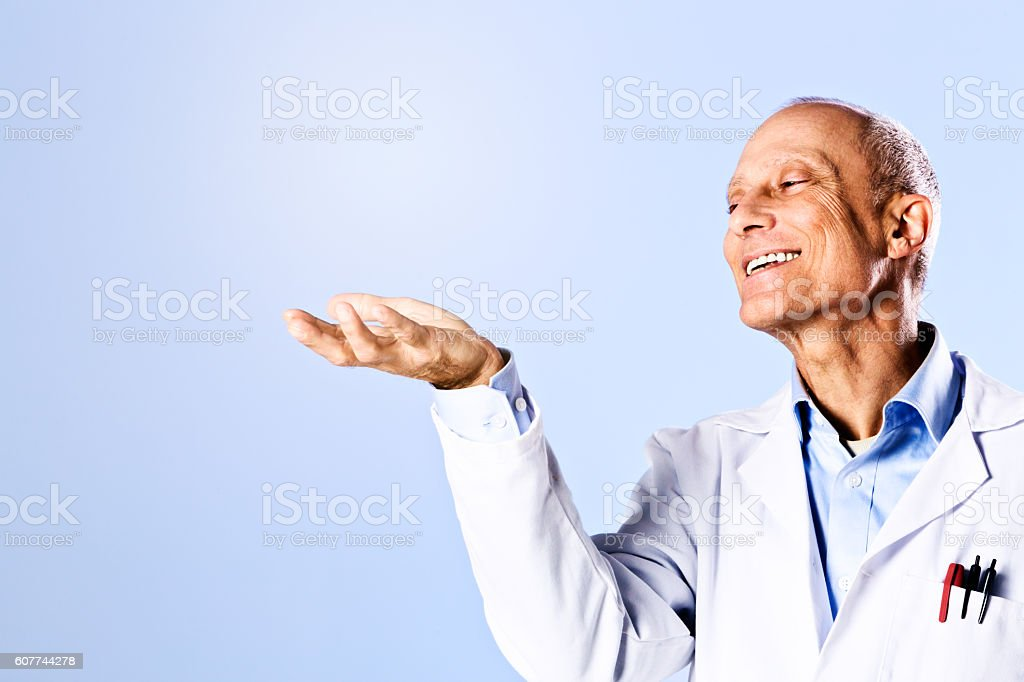 Smiling professional man looks at copy space he is supporting stock photo