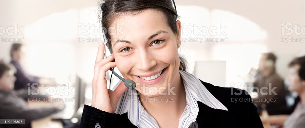 A smiling professional woman talking on a headset royalty-free stock photo