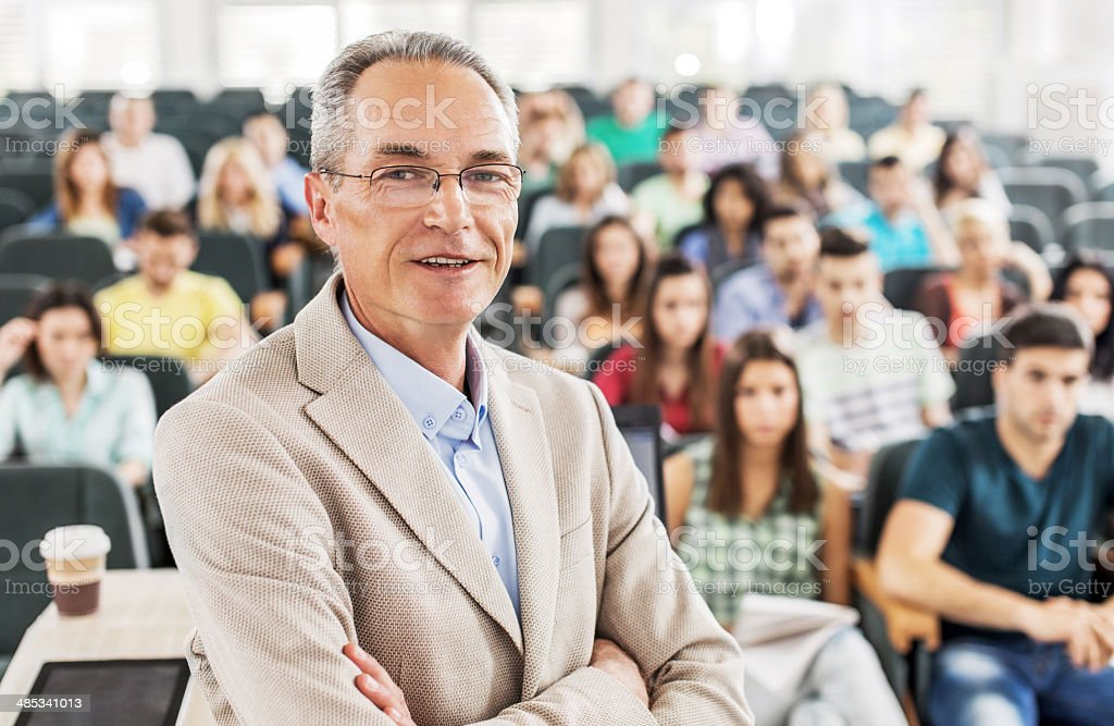 Smiling professor in the classroom. stock photo