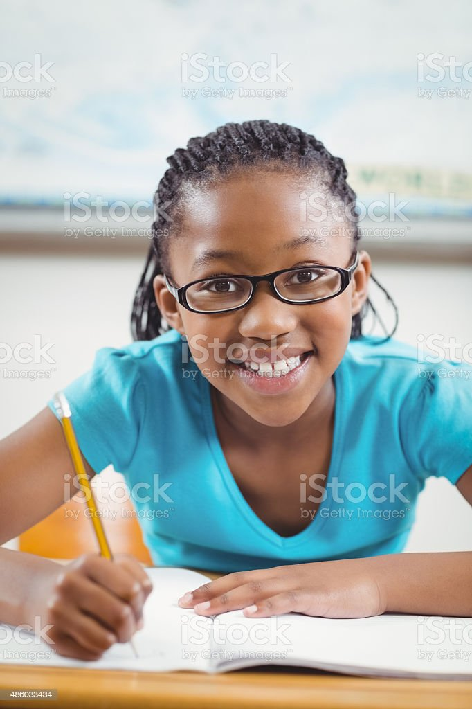 Smiling pupil working at her desk in a classroom stock photo