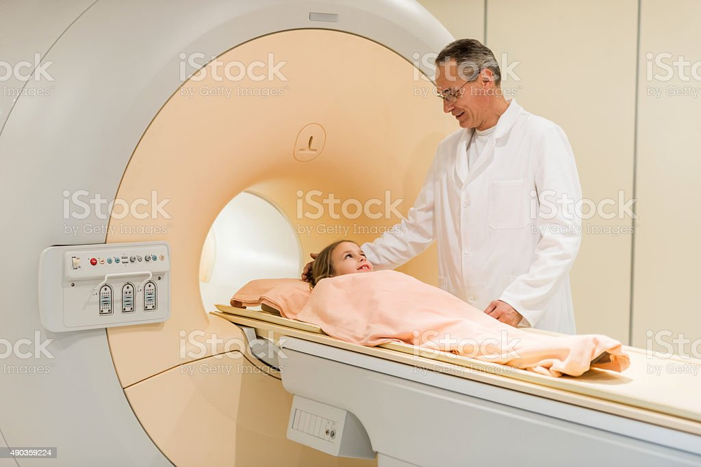 Smiling radiologist talking to little girl before MRI scan. stock photo