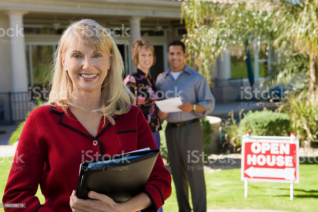 Smiling Real Estate Agent with New Homeowners stock photo