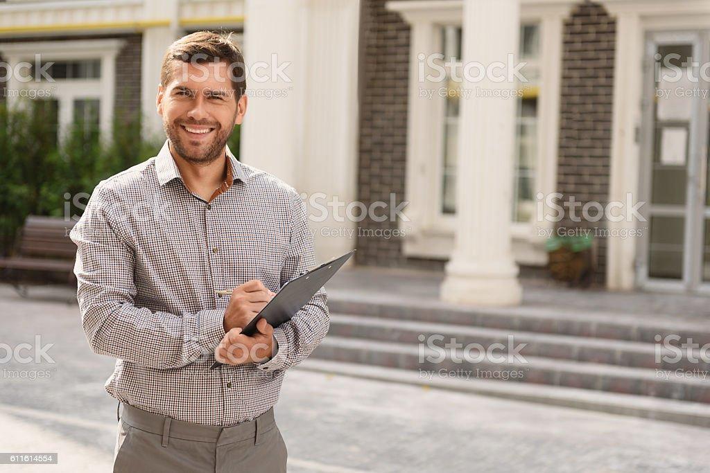 Smiling realtor standing outside modern house stock photo