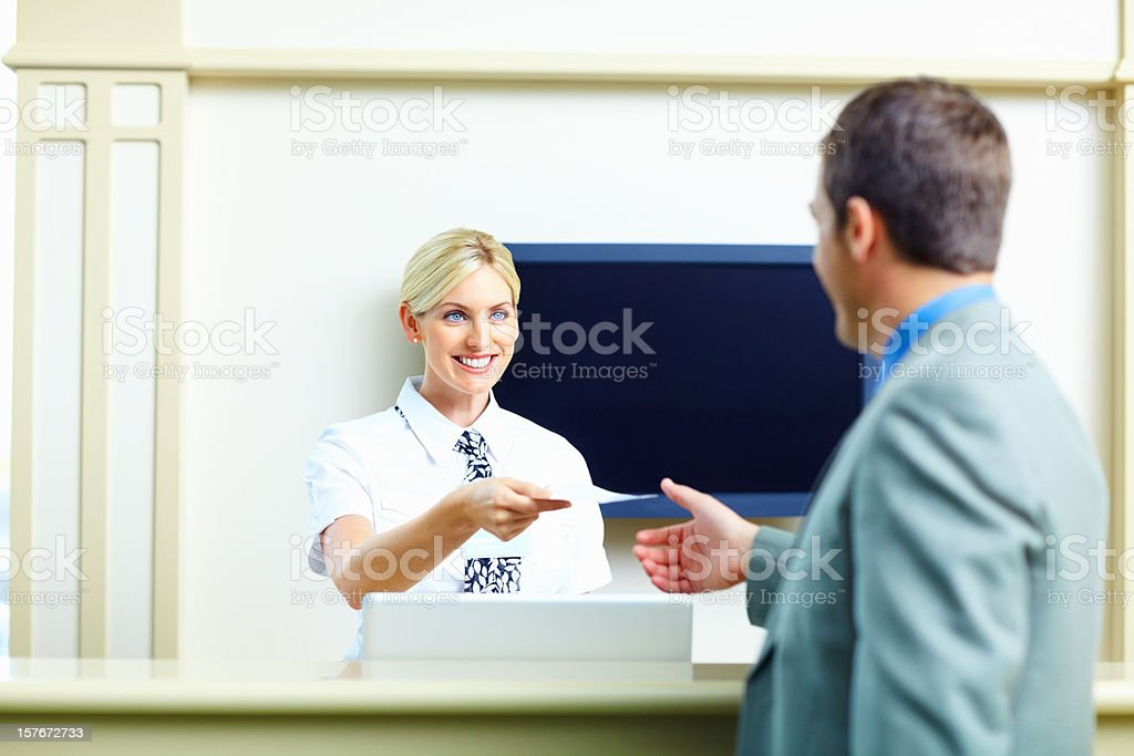 Smiling receptionist giving an airline ticket to business man stock photo