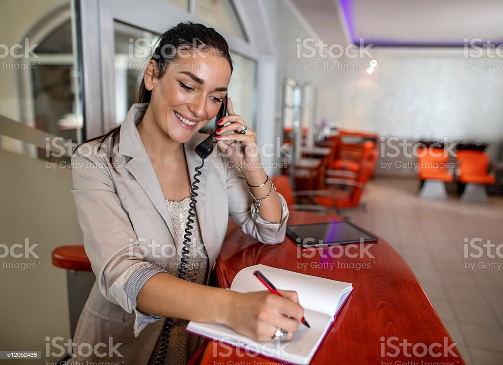 Smiling receptionist making appointment over the phone. stock photo