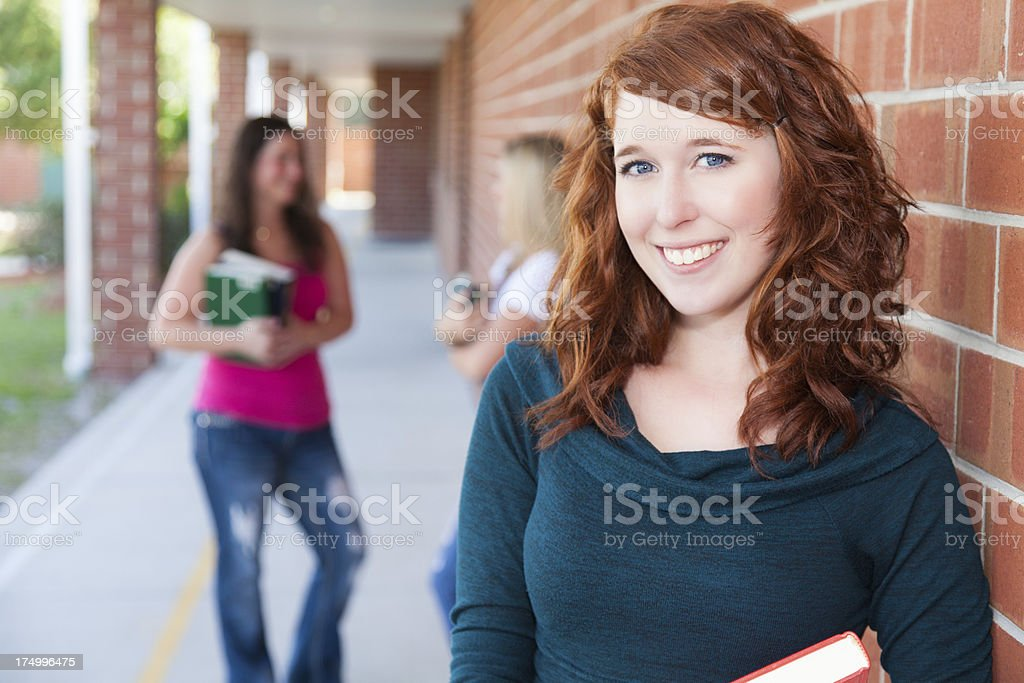 Smiling red haired college or high school student on campus royalty-free stock photo