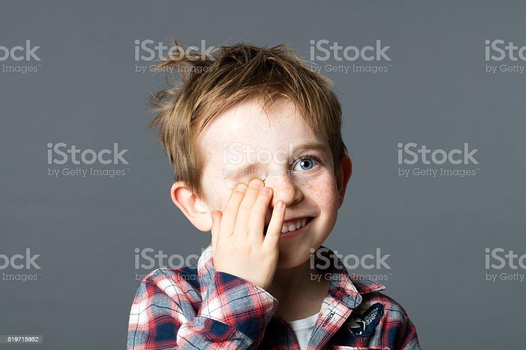 smiling red-hair child hiding one eye for fun eyesight stock photo