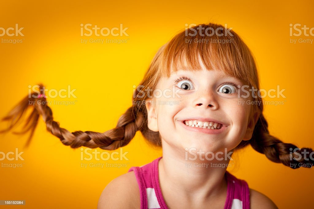 Smiling Red-Haired Girl with Upward Braids and Excited Look royalty-free stock photo