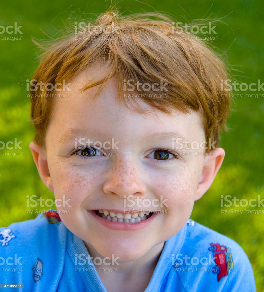 Smiling Redhead Freckle Face Happy Boy in Pajamas stock photo