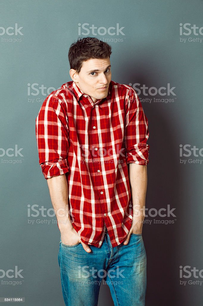 smiling reserved young man shrugging for shyness and shame stock photo
