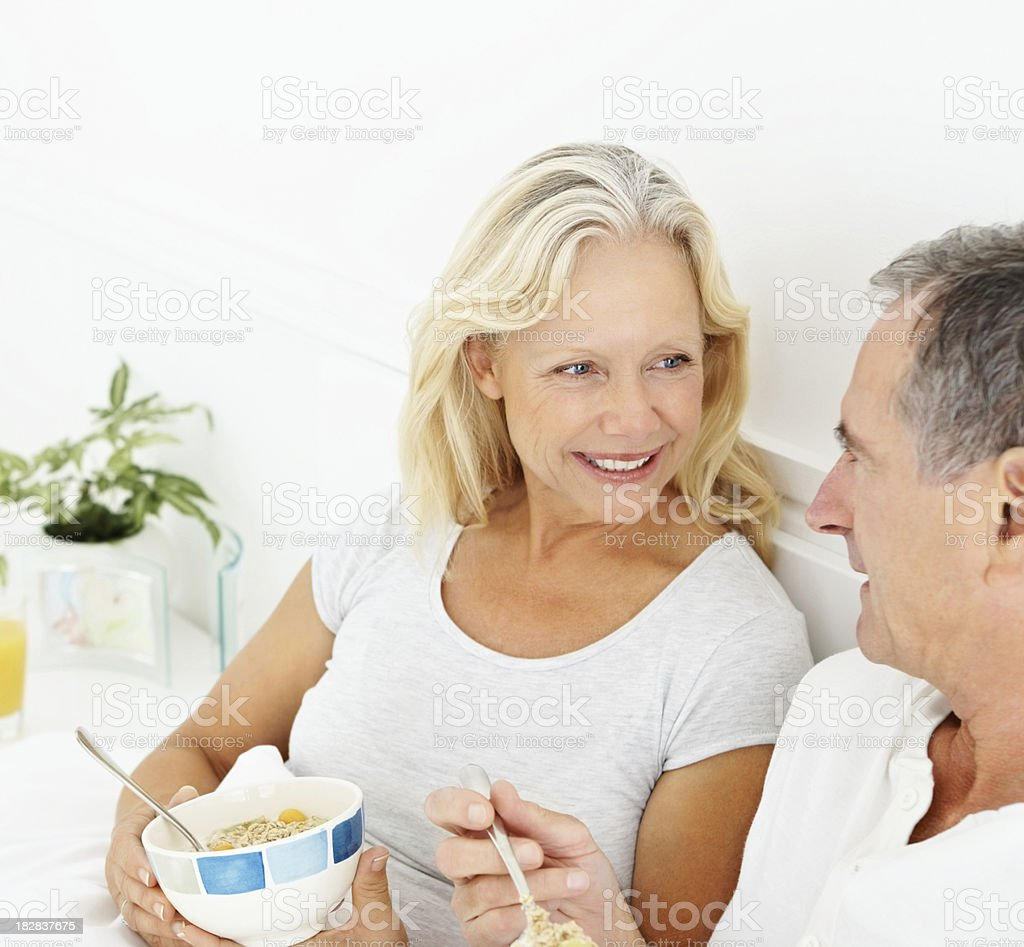 Smiling retired couple eating their breakfast royalty-free stock photo
