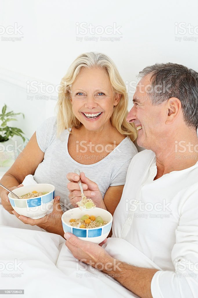 Smiling retired couple having their breakfast in bed royalty-free stock photo