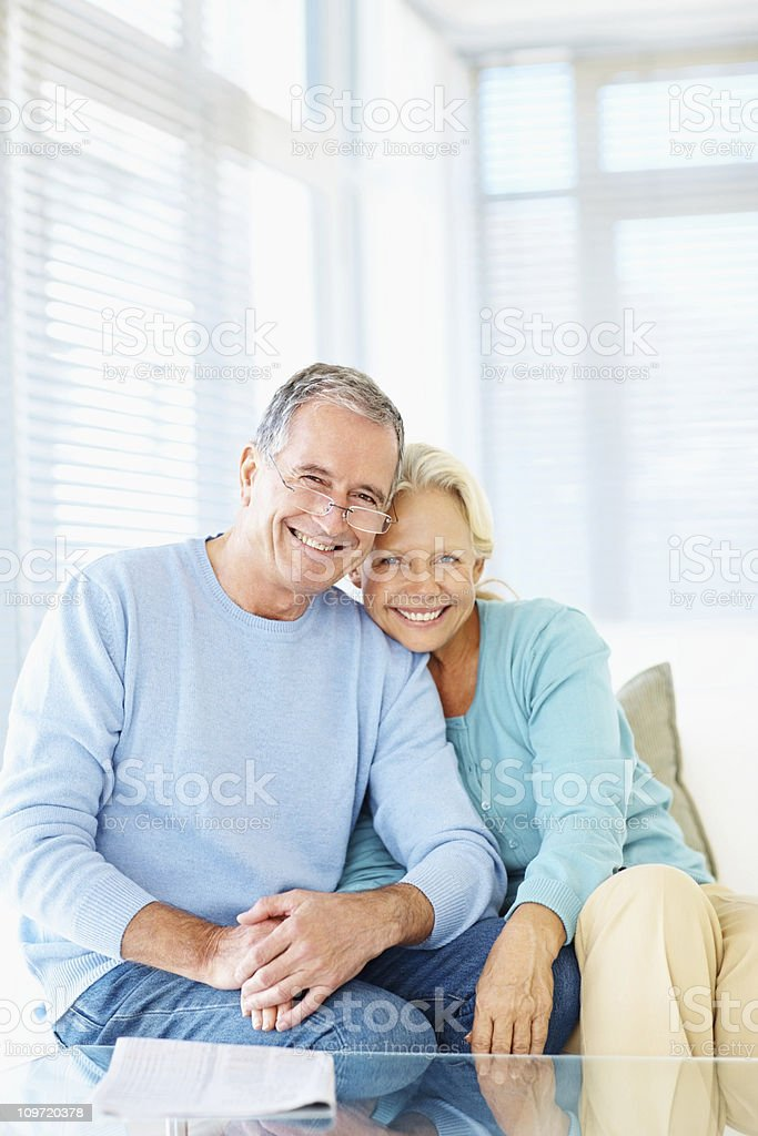 Smiling retired couple sitting together at home stock photo