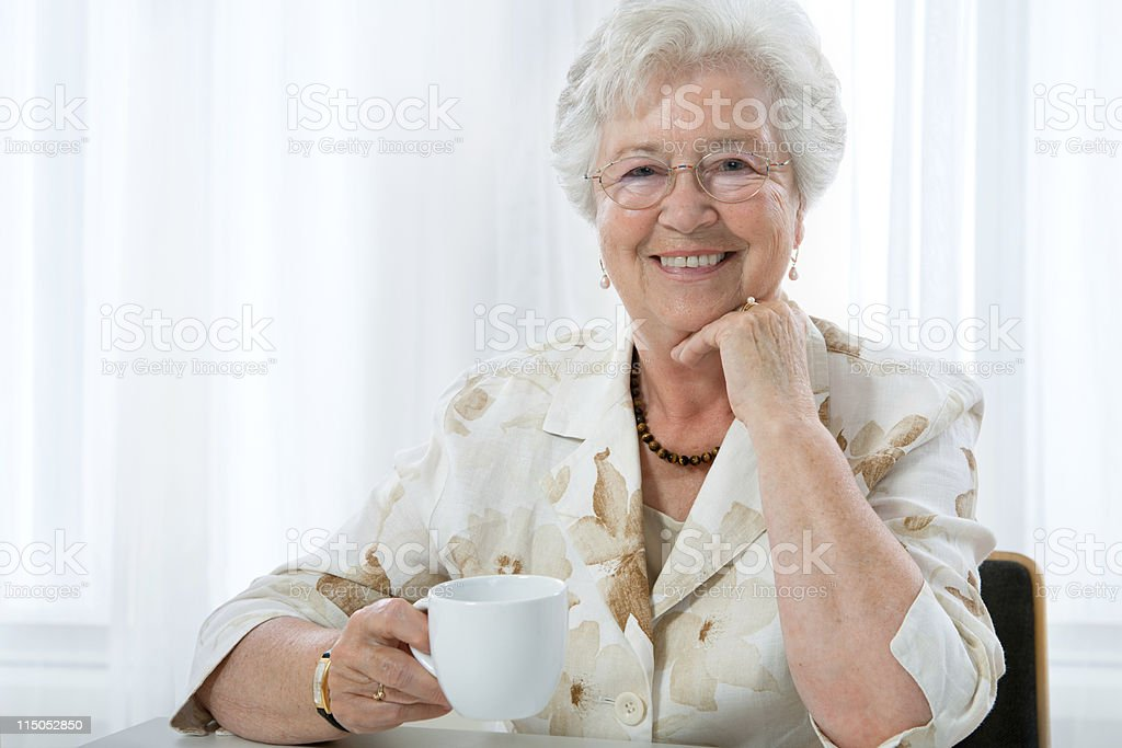 Smiling retired lady drinking a cup of coffee  royalty-free stock photo