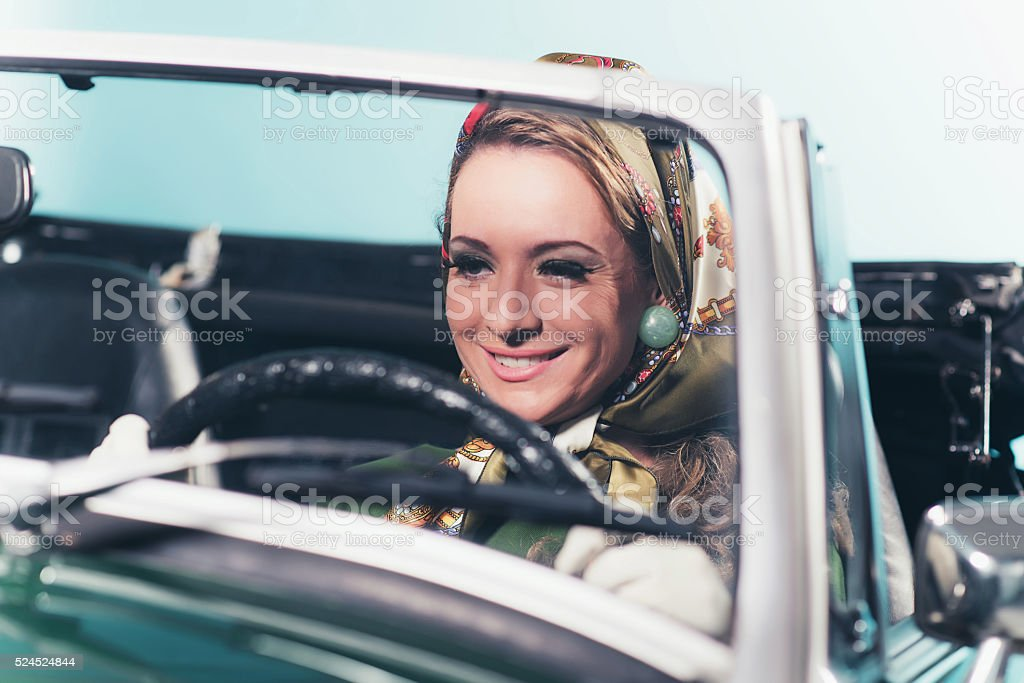 Smiling retro 1960s fashion woman with headscarf driving sports car. stock photo
