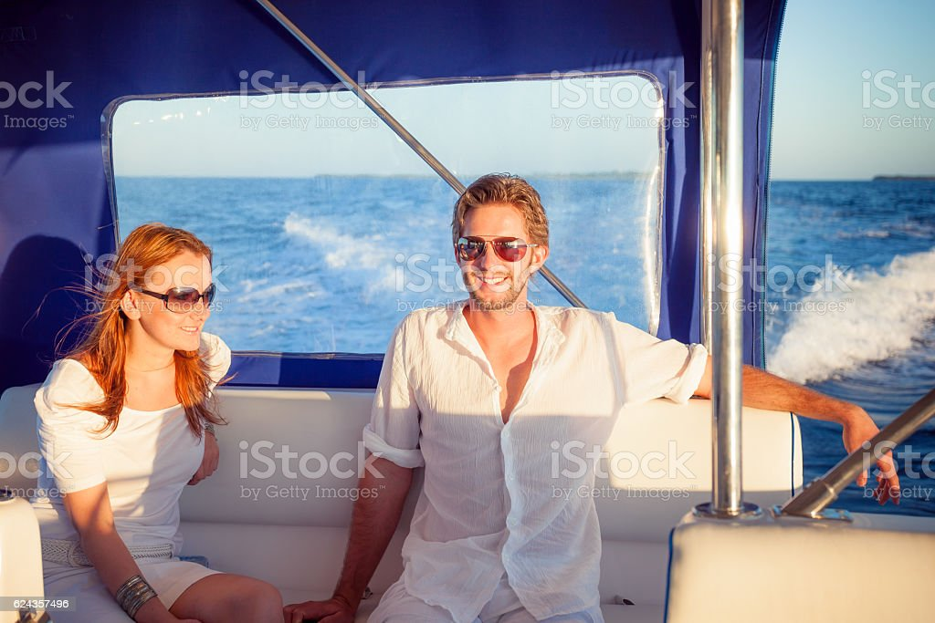 smiling rich couple motor boat stock photo