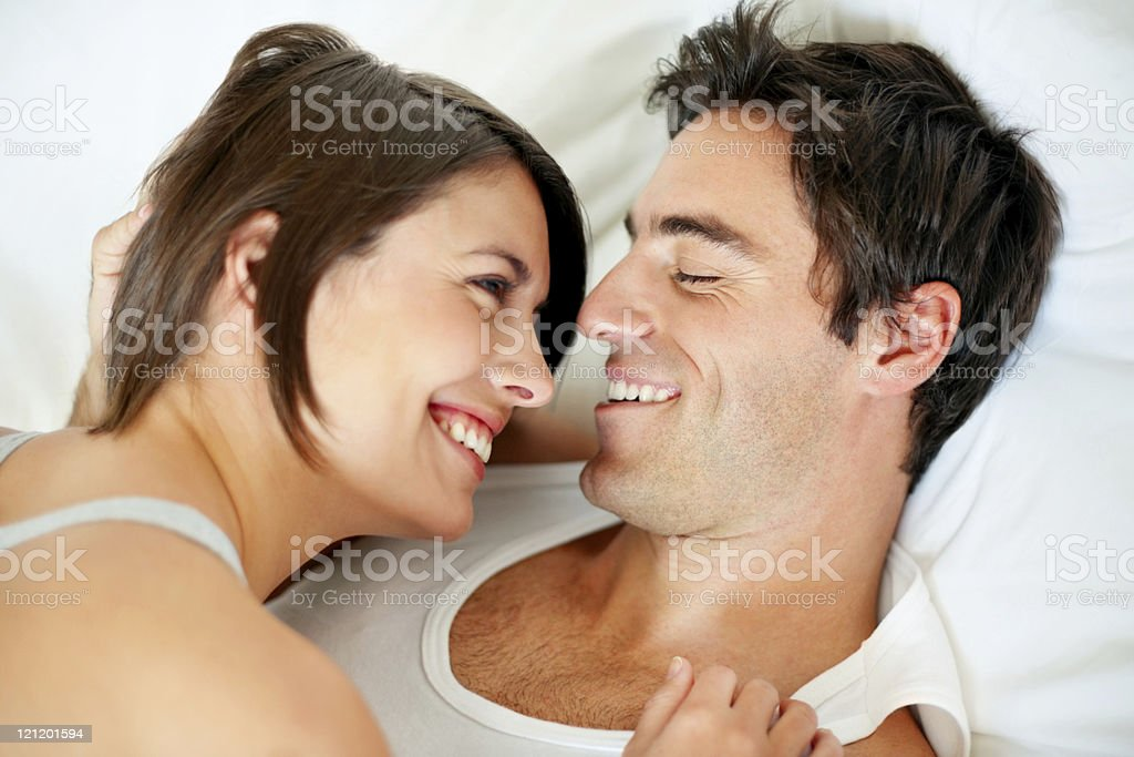 Smiling romantic couple lying in bed stock photo