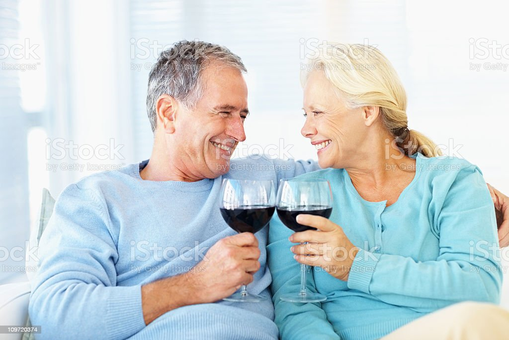 Smiling romantic couple toasting wine glasses royalty-free stock photo