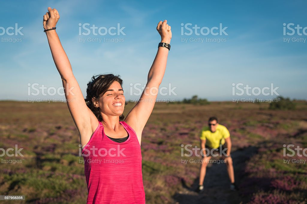 Smiling runner woman rising her arms after wining trail running stock photo