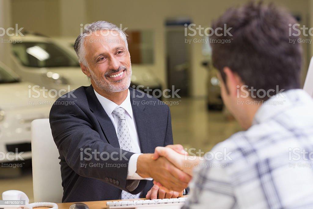 Smiling salesman shaking a customer hand stock photo