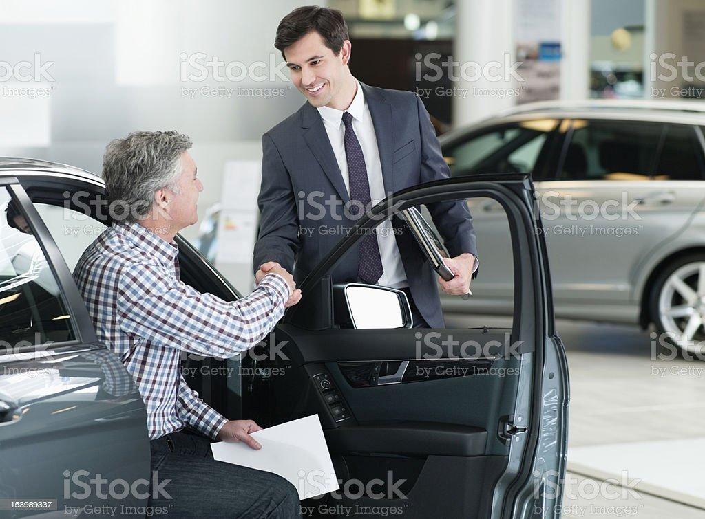 Smiling salesman shaking manÕs hand in car dealership showroom stock photo