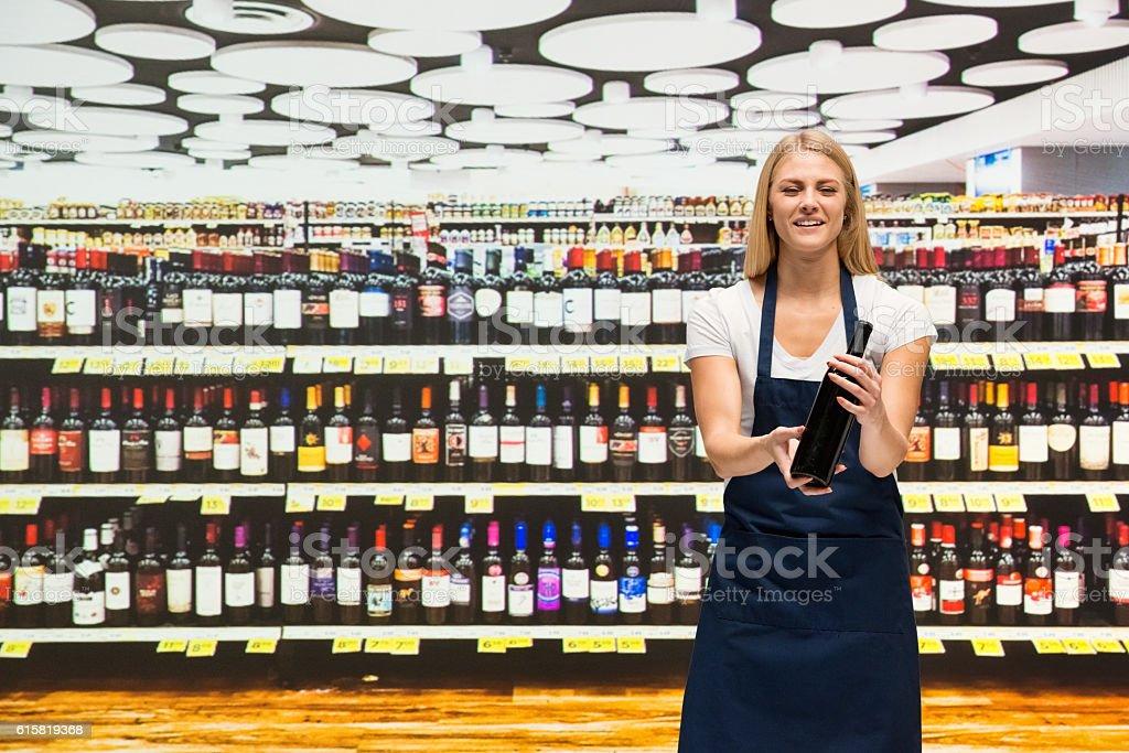Smiling saleswoman in supermarket stock photo