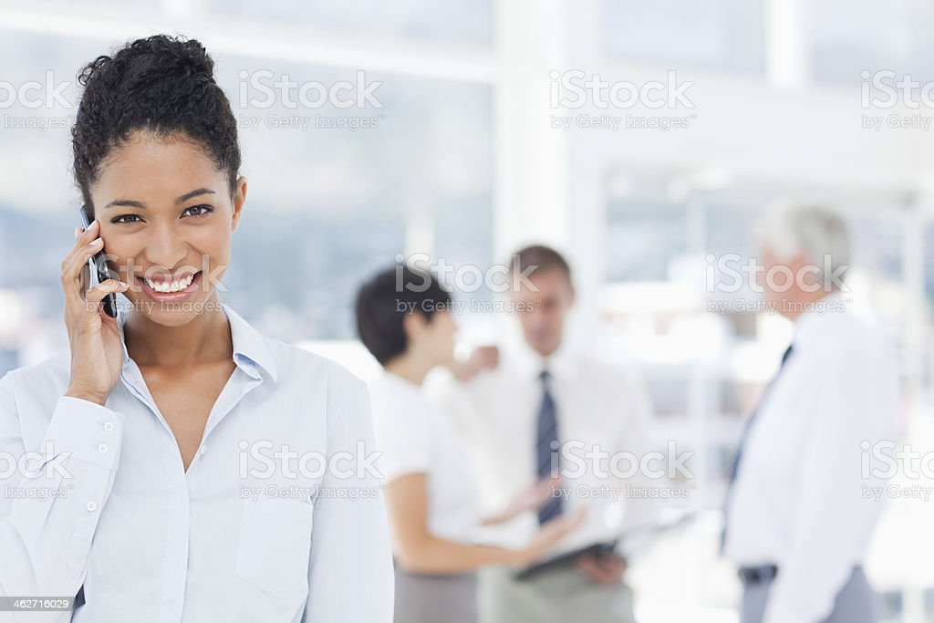 Smiling saleswoman on her cellphone with colleagues behind stock photo
