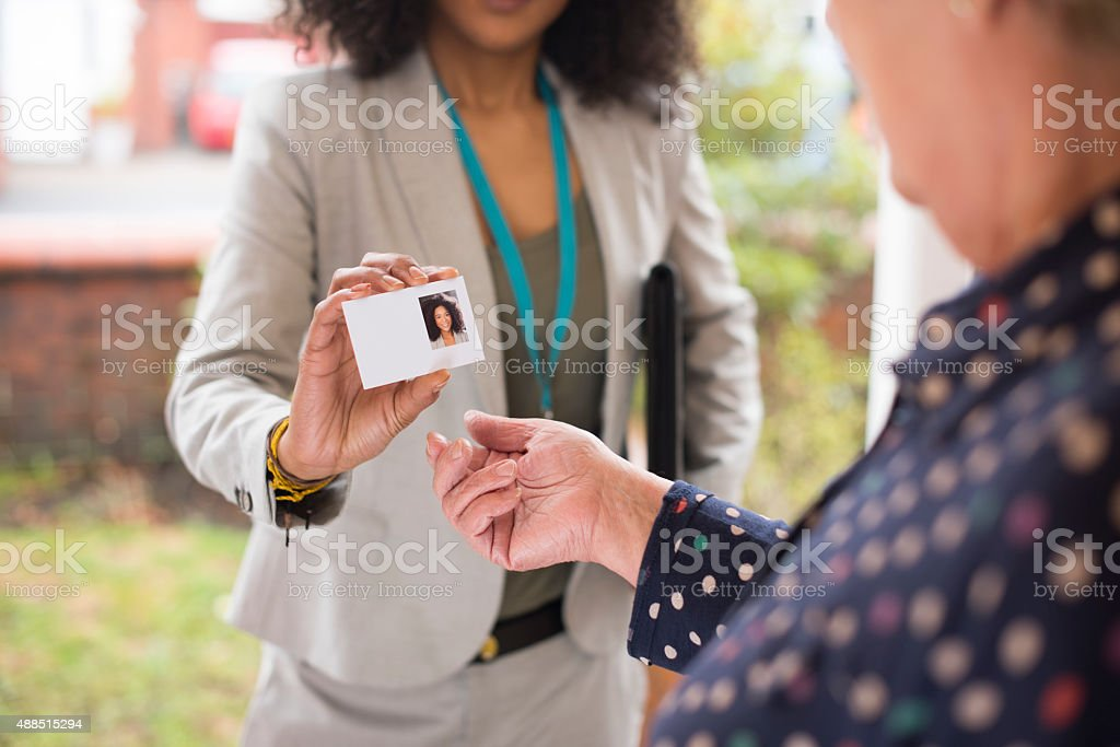 Smiling saleswoman presents her card at the door . stock photo