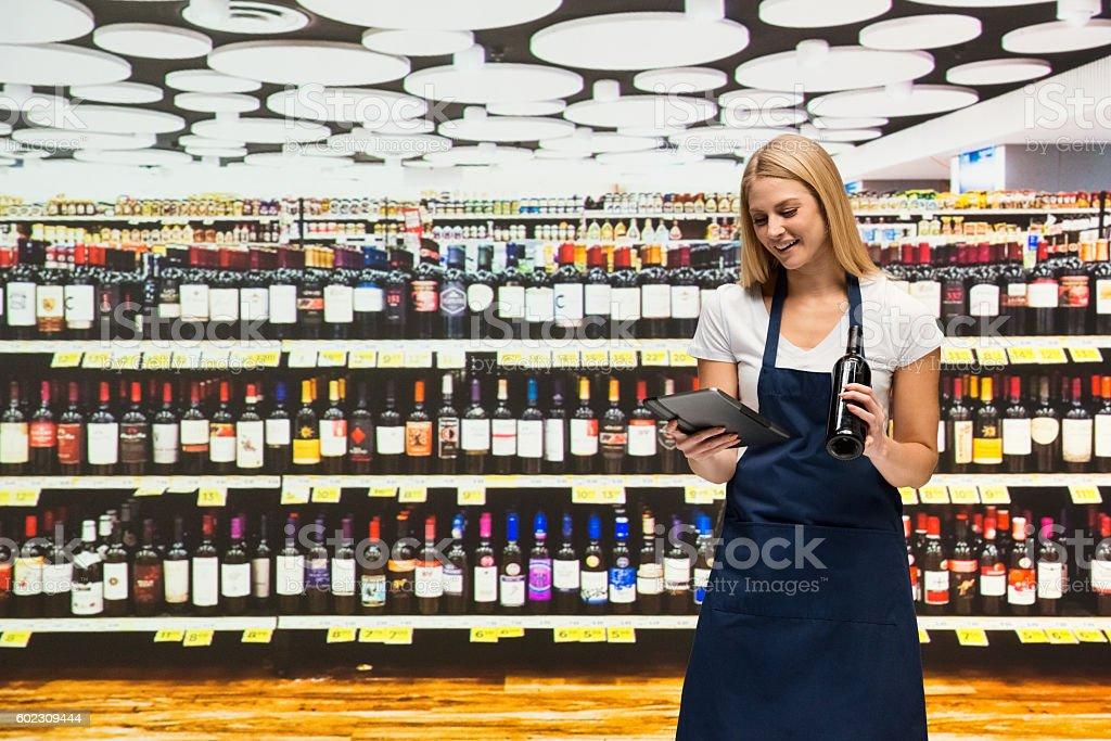 Smiling saleswoman using tablet in supermarket stock photo