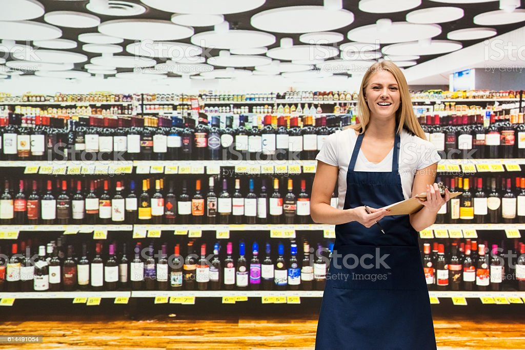 Smiling saleswoman working in shopping mall stock photo