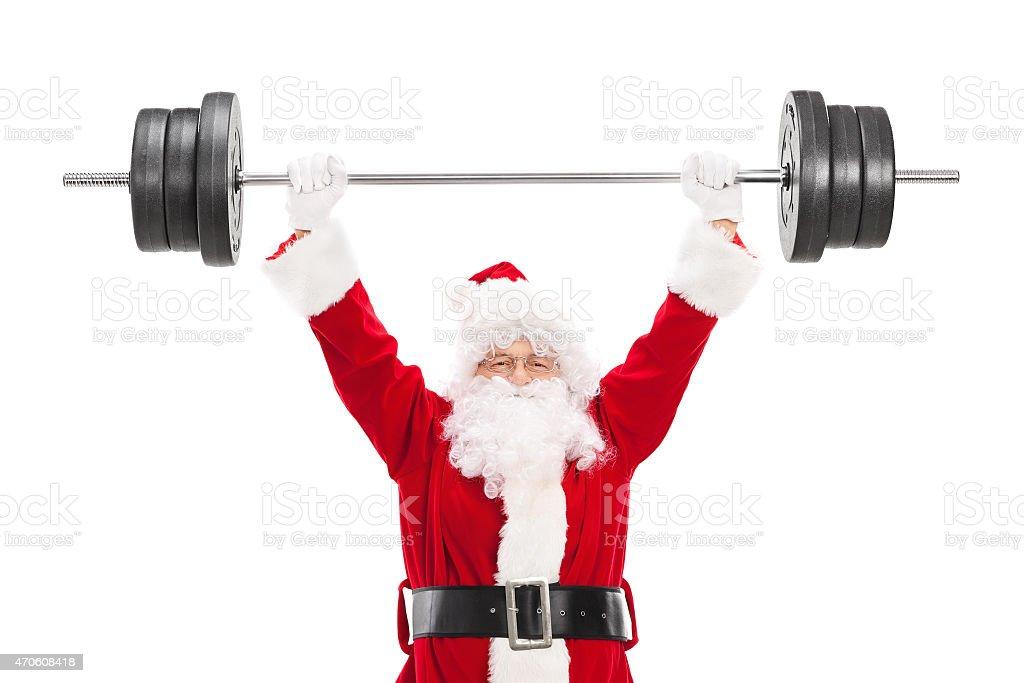Smiling Santa Claus lifting a heavy barbell stock photo