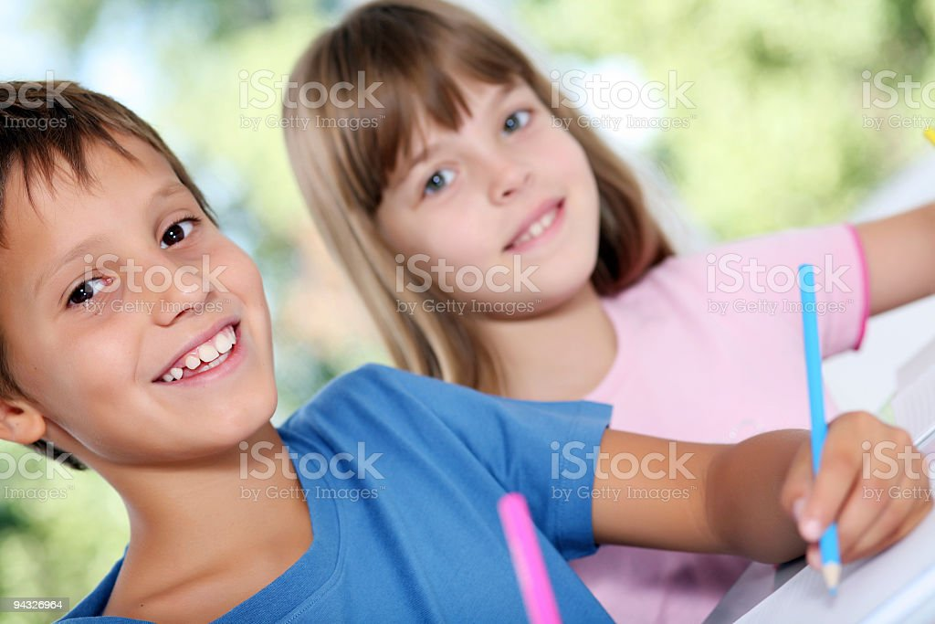 Smiling schoolchildren draws a picture. royalty-free stock photo