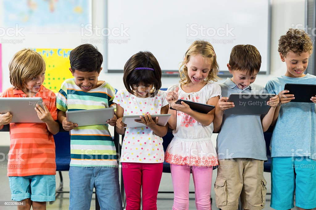 Smiling schoolchildren using digital tablet stock photo