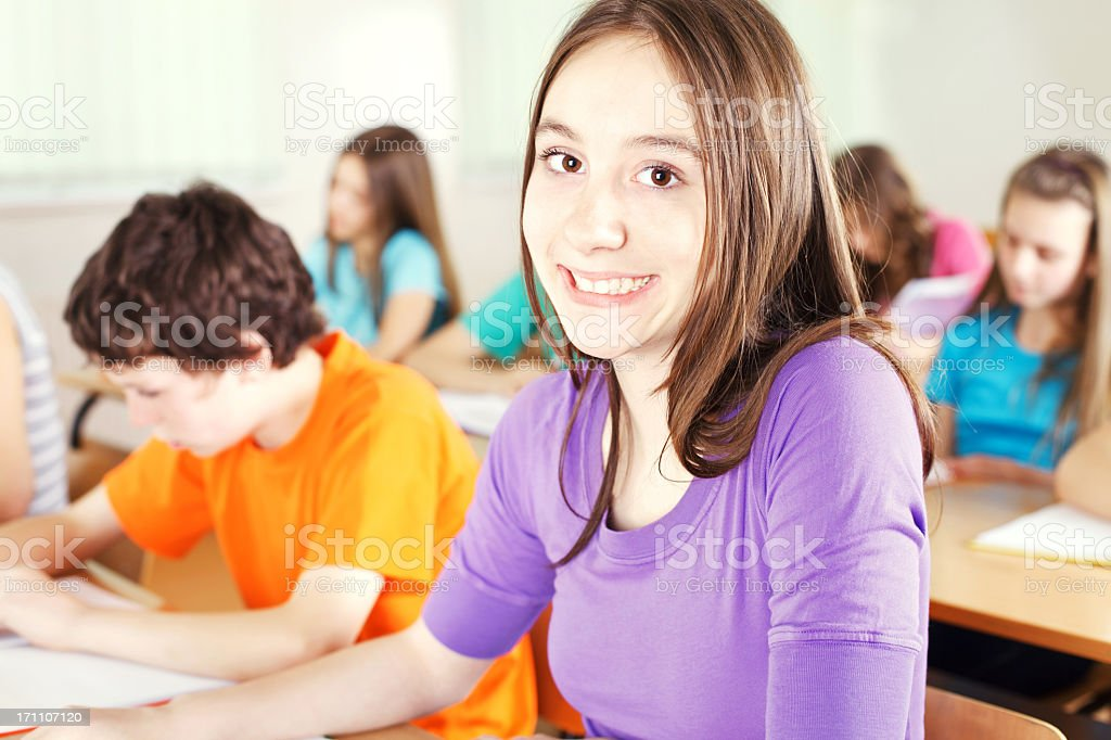 Smiling schoolgirl in the classroom, looking at camera royalty-free stock photo