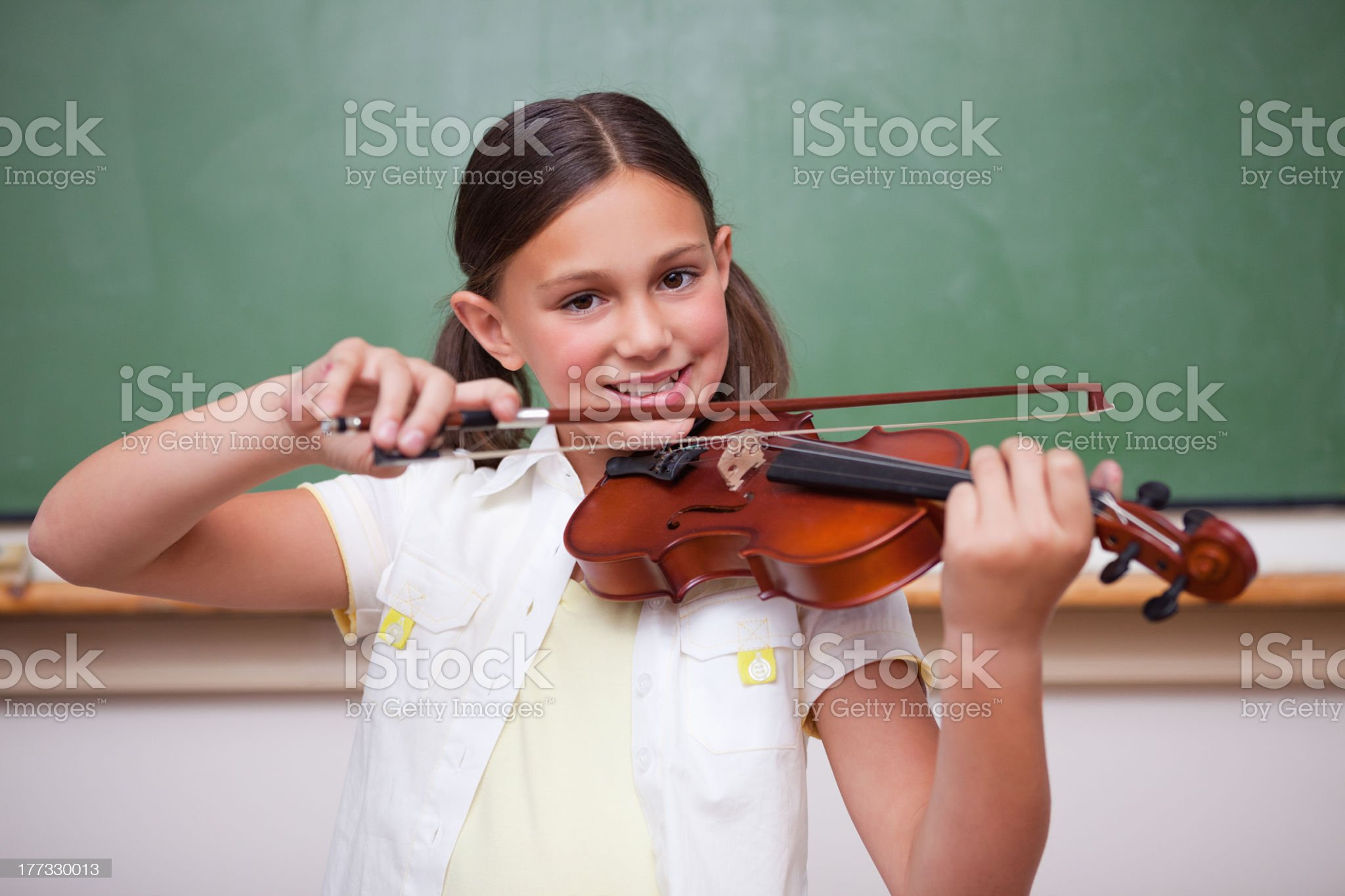 Smiling schoolgirl playing the violin royalty-free stock photo